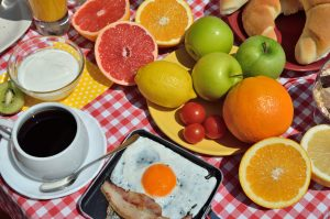 Breakfast or brunch with cup of fresh coffee, ham and eggs, Greek yogurt, cereals, croissants and colorful fruits served on red-white tablecloth