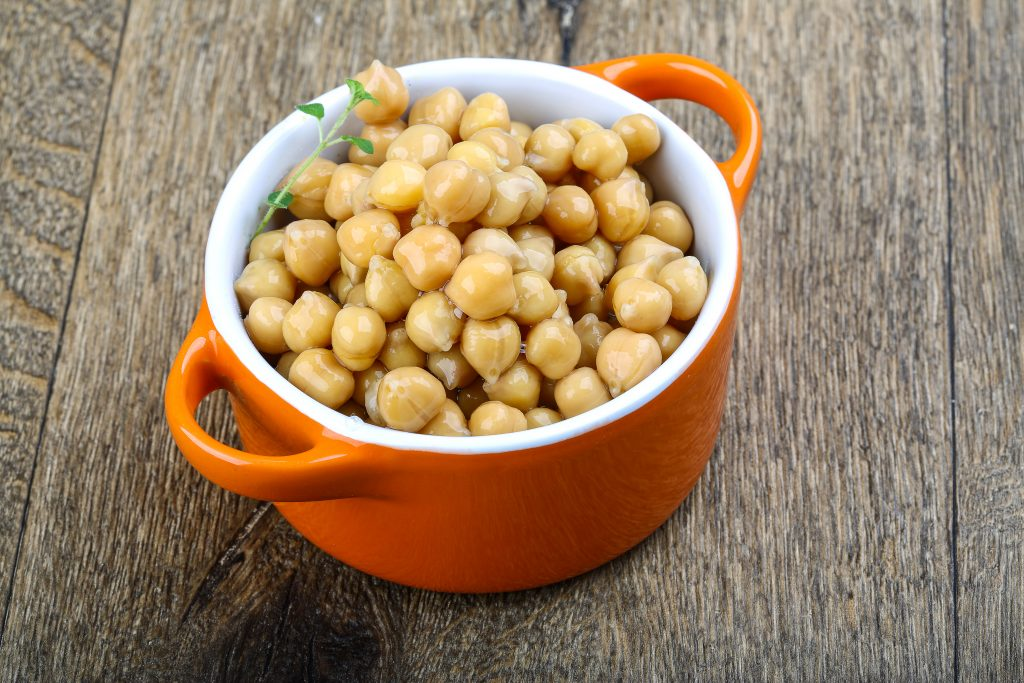 Canned chickpeas in the bowl on wood background